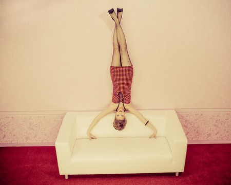 Charming fashionable woman standing on a sofa upside down. photo