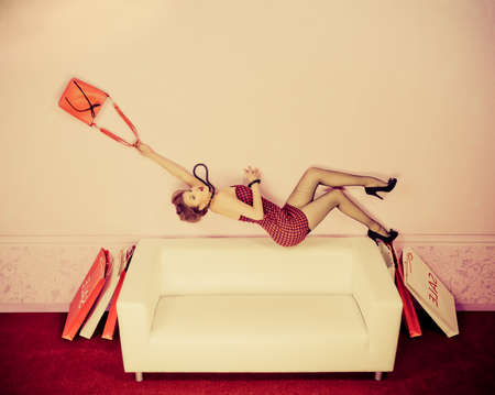 Charming fashionable woman flying over the sofa in the room with her bag. Sepia. photo