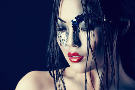 bizarre: Portrait of an asian model with fantasy make-up. Black background.