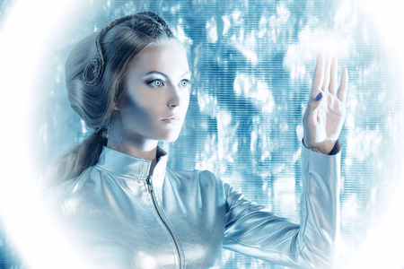 latex woman: Beautiful young woman in silver latex costume with futuristic hairstyle and make-up. Touchscreen. Sci-fi style.