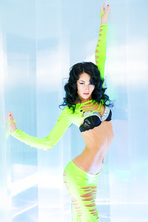 Modern brunette girl dancer in a sexual costume dancing in a futuristic interior. photo