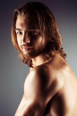 hombres sin camisa: Retrato de un hombre desnudo musculoso sexual que presenta sobre fondo oscuro.