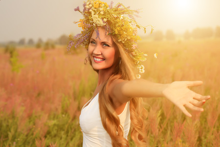 circlet: Portrait of a romantic smiling young woman in a circlet of flowers outdoors.