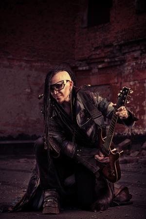 modern rock: Modern rock musician playing the guitar outdoor.