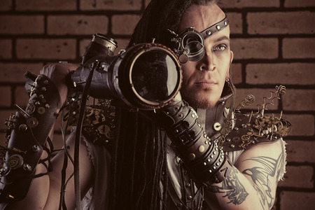 Portrait of a steampunk man with a mechanical devices over brick wall. photo