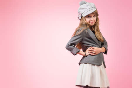 Portrait of a pretty ten years girl in autumn hat smiling at camera. Pink background. Stock Photo - 22880975