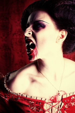 bloodthirsty: Portrait of a bloodthirsty female vampire over red vintage background.