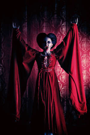 fantasy makeup: Portrait of a bloodthirsty female vampire over red vintage background.