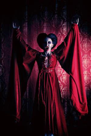maquillaje de fantasia: Retrato de un vampiro sediento de sangre femenina sobre fondo rojo del vintage.