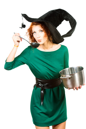 Charming red-haired witch brews a witchs brew. Halloween. Isolated over white.  photo