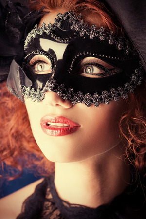 Portrait of a beautiful smiling woman in carnival mask. photo