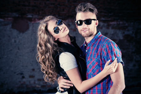 Couple of happy young people in love posing outdoors over brick wall. photo