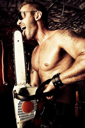 violence in the workplace: Hombre musculoso guapo expresivo con una motosierra en el viejo garaje.