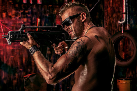 Portrait of a handsome muscular soldier man holding a machine gun photo