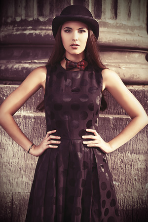 Beautiful brunette standing on the street of the old town. Retro style. photo