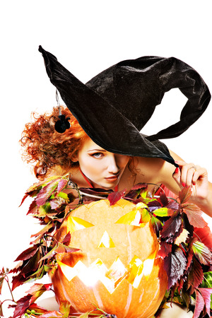 Beautiful red-haired witch casts a spell over pumpkins  Halloween  Isolated over white  photo