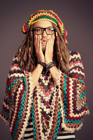 Portrait of a rastafarian young man holding hands on face  photo