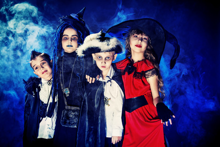 Cheerful children in halloween costumes posing over dark background. photo