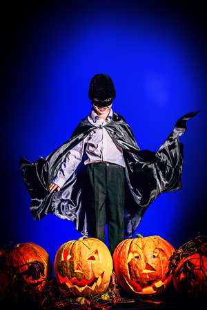 Little boy in halloween costume posing with pumpkins. Over dark background. photo