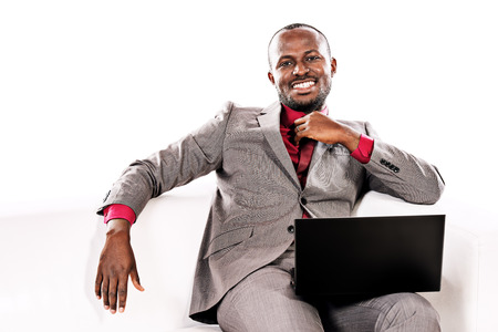 Portrait of a handsome african american business man working on his laptop on a sofa. Isolated over white. photo