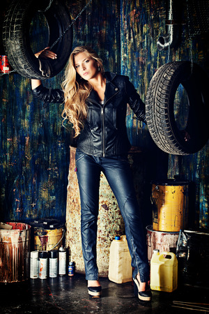 black pants: Stunning blonde woman in black leather jacket and pants standing in the old garage.