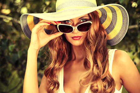 Beautiful young woman in elegant hat and sunglasses posing outdoor. Stock Photo - 23199779