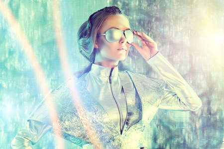 Beautiful young woman in silver latex costume and glasses with futuristic hairstyle and make-up. Sci-fi style. photo
