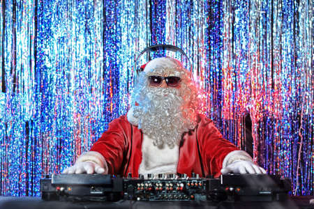 christmas music: DJ Santa Claus mixing up some Christmas cheer. Disco lights in the background.