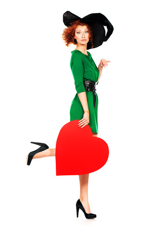 Full length portrait of a charming red-haired witch holding red heart. Halloween. Isolated over white.