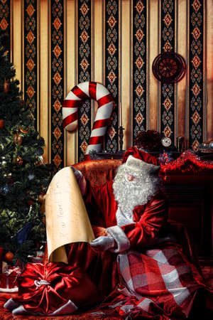 comfortable chair: Santa Claus with a list of Christmas presents sitting in a comfortable chair near the fireplace at home.