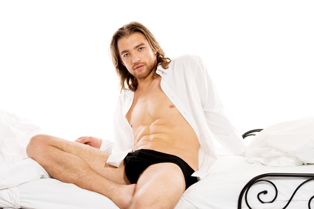 Handsome man in an unbuttoned white shirt sitting on a bed. Isolated over white. photo