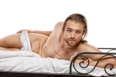 nudo maschile: Bel uomo nudo sdraiato in un letto. Isolato su bianco.