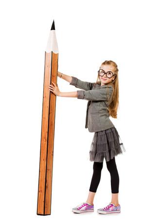 niños estudiando: Retrato de cuerpo entero de una linda niña de diez años en espectáculos sosteniendo un enorme lápiz. Educación. Aislado en blanco. Foto de archivo