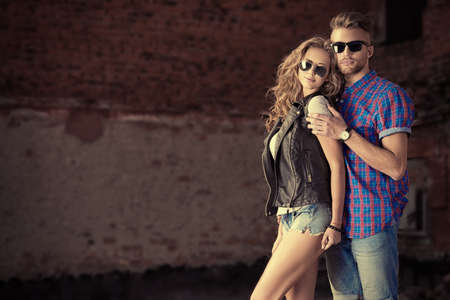 homem: Casal de jovens em roupas jeans levanta ao ar livre sobre a parede de tijolos. Imagens