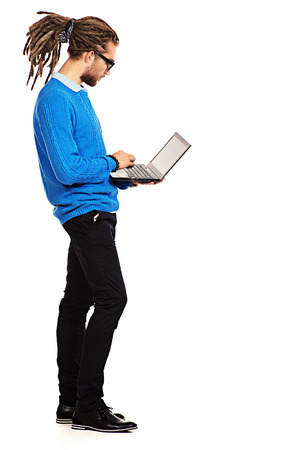 Full length portrait of a modern handsome young man in spectacles standing with his laptop. Isolated over white. photo