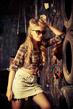 Charming pin-up woman with retro hairstyle and make-up in the old garage. photo