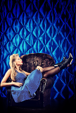 Charming pin-up woman with retro hairstyle and make-up sitting in the armchair over vintage . photo