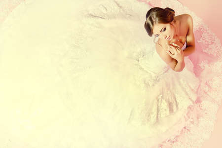 beautiful bride: Beautiful charming bride in a luxurious dress looking up. Over pink . Stock Photo
