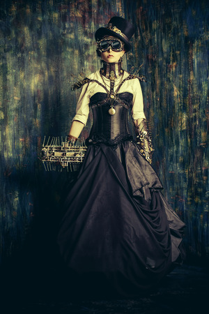 Portrait of a beautiful steampunk woman over grunge wall. photo