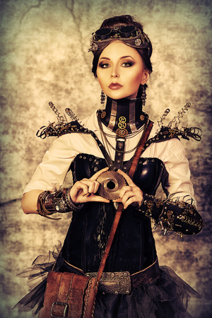 Portrait of a beautiful steampunk woman over grunge wall. Stock Photo - 23473477