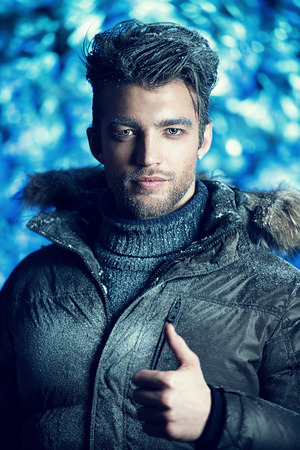 Portrait of a handsome man dressed in winter clothes, covered with frost. photo