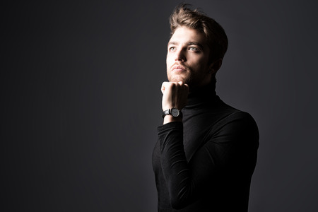 Modern handsome young man in black pullover posing over dark background. photo