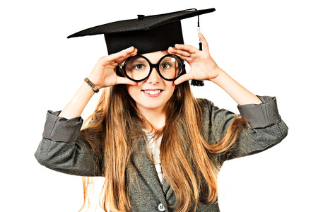 Portrait of a pretty ten years girl in big round spectacles and academic hat. Isolated over white. photo