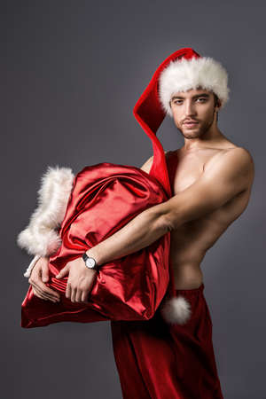 Portrait of a sexual young man in Christmas hat holding bag with gifts.  photo