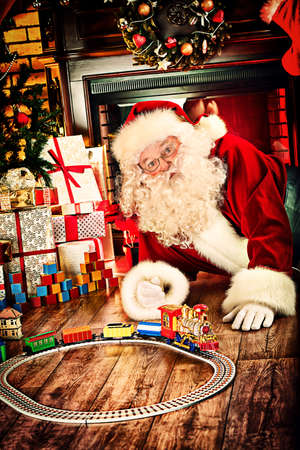 Santa Claus playing with toys under the Christmas tree. Stock Photo - 23550622
