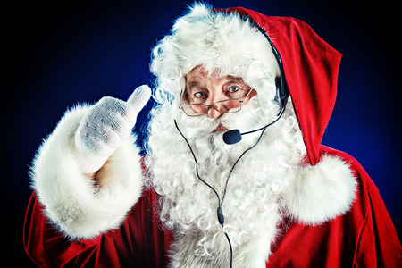 Portrait of a modern Santa Claus in wearing headset. Over black background.  photo