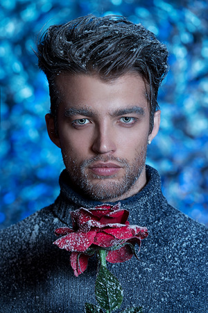 Portrait of a handsome man dressed in winter clothes and holding a rose, covered with snow. photo