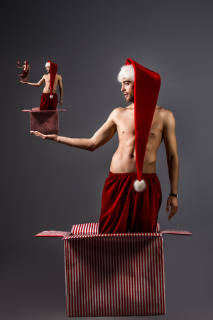 Portrait of a sexual young man in Christmas hat.  photo