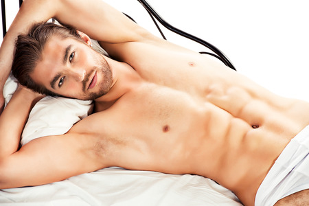 nude man: Handsome nude man lying in a bed. Isolated over white. Stock Photo