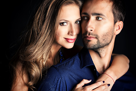 Portrait of a beautiful young couple in love posing at studio over black background. photo